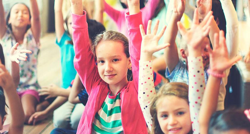 Een foto van een groep blije kinderen met de handen in de lucht