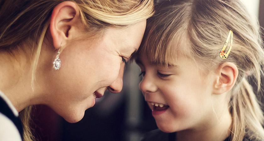 Een foto van een moeder en dochter met de liefdevol de hoofden tegen elkaar aan
