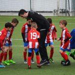 Een foto van een groep kinderen in voetbaltenues met hun trainer