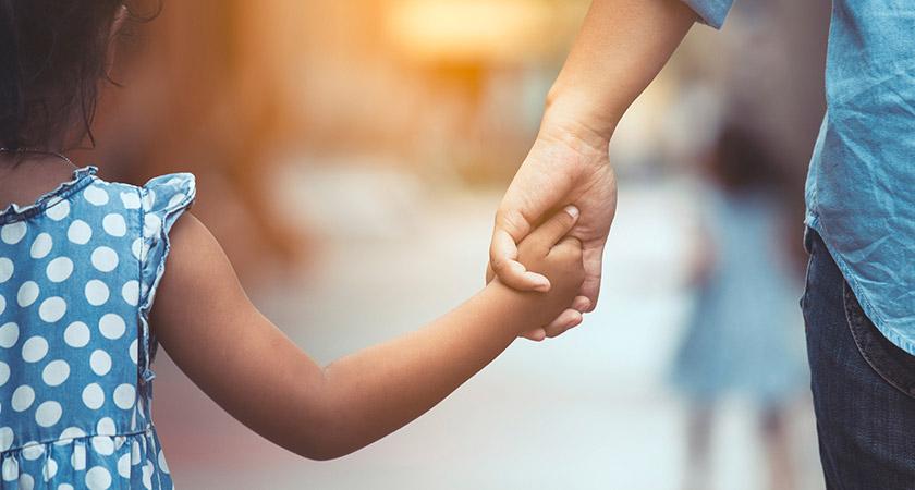 Een foto van hand in hand lopende ouder en kind