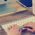 handen typen op toetsenbord van computer