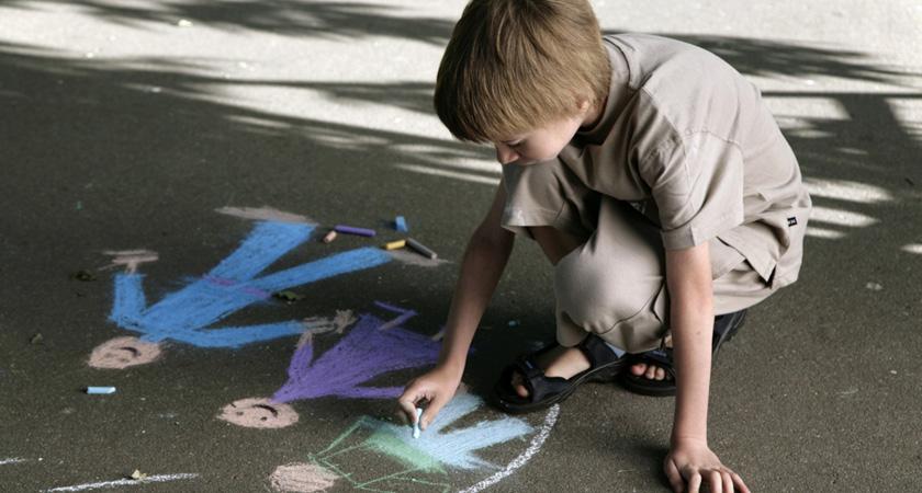 kind tekent met stoepkrijt een gezin